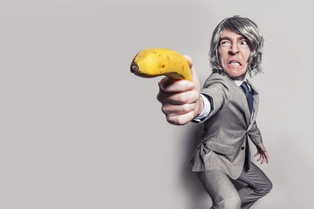 Annoyed business man pointing a banana